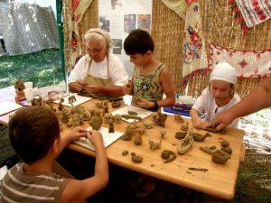 Copiii învață sa creeze figurine sub îndrumarea meșterului olar.
